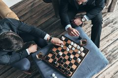 Think hard before the move. Top view of young thoughtful men in full suits playing chess while sitting indoors royalty free stock photos