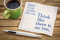 Think like there is no box. Don't think outside the box. Think like there is no box.- handwriting on a napkin with a cup of espresso coffee royalty free stock photos