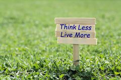Think less live more. Wooden sign in grass,blur background Royalty Free Stock Photos