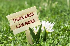 Think less live more. On wooden sign in garden with white spring flower Royalty Free Stock Photography