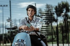 Sincere optimistic guy reconsidering answer on motorbike royalty free stock photos
