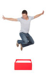 Think out of the box. Young man jumping out a red box stock image