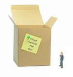 Think outside the box. Metaphor with businessman looking at a cardboard box royalty free stock image