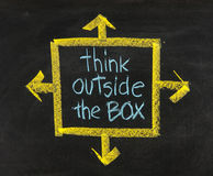 Think outside the box. Concept of different or unconventional thinking sketched with white chalk on a blackboard with eraser smudges royalty free stock photography