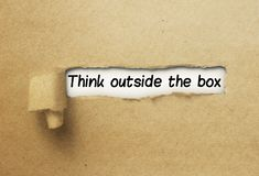 Think outside the box behind ripped curl paper behind ripped curl paper. Think outside the box behind ripped curl paper text behind ripped curl paper stock photo