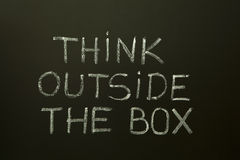 THINK OUTSIDE THE BOX on a blackboard. Concept image about unconventional or different thinking. 'Think outside the box' handwritten with white chalk on a royalty free stock images