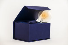 Think outside the box. Bulb in blue box against white background with copy space signifying thinking outside the box concept stock photography