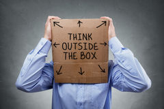 Think outside the box. Businessman with cardboard box on his head saying think outside the box concept for brainstorming, creativity, innovation, strategy or stock photos