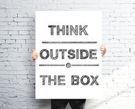 Think outside the box. Businessman holding poster with think outside the box stock photography