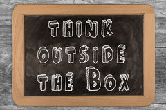 Think outside the box - chalkboard with outlined text. On wood Royalty Free Stock Photography