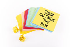 Think Outside The Box. Colorful adhesive note papers' stack with THINK OUTSIDE THE BOX note Stock Image