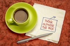 Think outside the box concept. Hadwriting on a napkin with a cup of coffee royalty free stock images