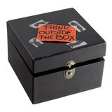 Think outside the box concept or reminder. Think outside the box - orange label (reminder note) casually taped on top of old black painted wooden box with dents Royalty Free Stock Photo