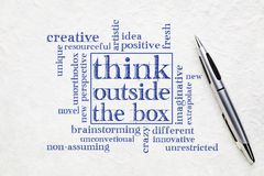 Think outside the box concept. Word cloud on a textured white paper with a pen royalty free stock photo