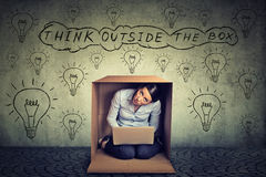 Think outside the box concept. Woman sitting inside box using working on laptop computer royalty free stock image