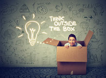 Think outside box concept. Young woman coming out of box Stock Photos