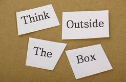Think Outside The Box. In cut out text on a background of brown cardboard. The well known phase applies to creative thinking and finding alternative solutions royalty free stock photography