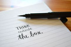 THINK OUTSIDE THE BOX hand-lettered in notebook. With brush calligraphy pen on wooden desk Stock Photos