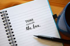 THINK OUTSIDE THE BOX hand-lettered in notebook. With brush calligraphy pen and cup of coffee on wooden desk Stock Photo