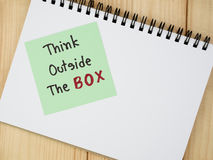"""Think outside the box 11. Handwriting word """"Think outside the box"""" on colorful note paper and notebook with wood background Stock Photo"""