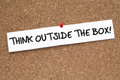 Think Outside The Box. Note pinned on cork noticeboard Stock Photo