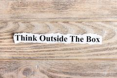 Think Outside The Box text on paper. Word Think Outside The Box on torn paper. Concept Image.  Royalty Free Stock Image