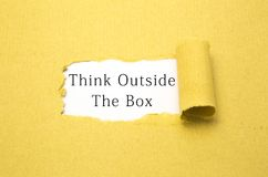 Think outside the box. Text on torn brown paper stock images