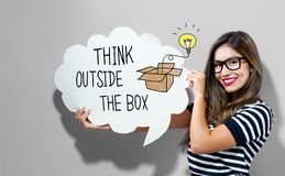 Think Outside The Box text with woman holding a speech bubble. Think Outside The Box text with young woman holding a speech bubble Stock Photo