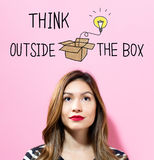 Think Outside The Box text with young woman. On a pink background Stock Photos
