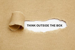 Think Outside The Box Torn Paper. Think Outside The Box appearing behind torn brown paper royalty free stock photography