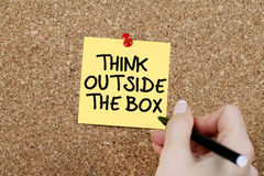 Think Outside The Box. Woman hand writing THINK OUTSIDE THE BOX on adhesive note pinned on cork noticeboard Royalty Free Stock Photo