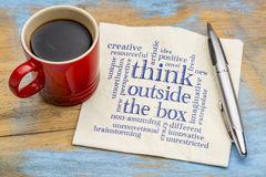 Think outside the box word cloud. Handwriting on a napkin with a cup of coffee royalty free stock photo