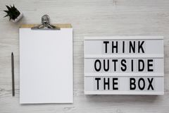 `Think outside the box` words on a light box, clipboard with blank sheet of paper over white wooden surface, top view. Flat lay,. Overhead, from above royalty free stock image