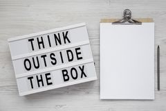 `Think outside the box` words on a light box, clipboard with blank sheet of paper on a white wooden background, top view. Flat l. Ay, overhead, from above. Copy stock images