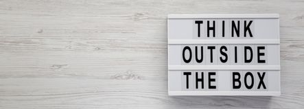 `Think outside the box` words on a lightbox on a white wooden surface, top view. Flat lay, overhead, from above. Space for text royalty free stock photography