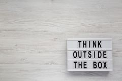 `Think outside the box` words on a modern board on a white wooden surface, top view. Flat lay, overhead, from above. Copy space stock photography