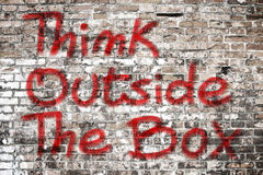 Think outside the box written on a brick wall - concept image royalty free stock photo