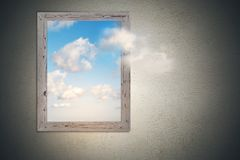 Think outside concept. Think outside the box concept with picture frame with bright sky with clouds inside at concrete wall background stock images