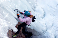 Think pink. Woman ice climber in pink coat with blue helmut ascending difficult route Stock Photo