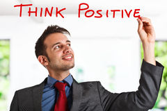 Think positive. Friendly businessman writing a positive concept on the screen Stock Image