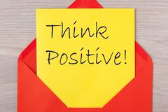 Think Positive Concept. Think Positive document in red envelope on wooden desk. Business concept royalty free stock photography
