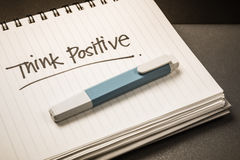 Think positive. Handwriting of Think Positive word as memo note on spiral notebook Stock Photos