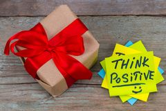 Think positive - inspirational handwriting in a green sticky not. E and gift with red ribbon on wooden background stock photo
