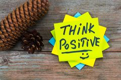 Think positive - inspirational handwriting in a green sticky not. E and pine cones on wooden background stock photos