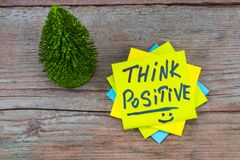 Think positive - inspirational handwriting in a green sticky not. E and christmas tree on wooden background stock image