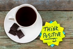 Think positive - inspirational handwriting in a green sticky not. E with a cup of coffee and a chocolate royalty free stock images