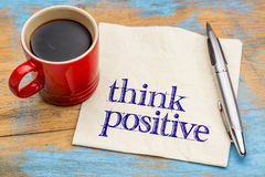 Think positive - napkin concept. Think positive - mindset concept on a napkin with a cup of coffee against grunge wood Stock Photo