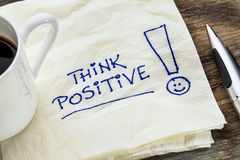 Think positive on a napkin. Think positive - motivational slogan on a napkin with a cup of coffee Stock Image
