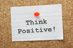 Think Positive!. The phrase Think Positive typed on a piece of paper and pinned to a cork notice board stock images