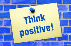 Think positive sign. Think positive text on yellow notepaper pinned to blue brick wall background royalty free stock photo